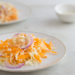 plate of mayo-free coleslaw with gold rim, on white tablecloth