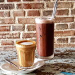 Glass of coffee and class of vegan chocolate milk on a wooden table near a brick wall