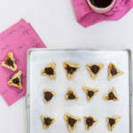 baking tray with hamantaschen and pink napkin with hamantaschen on top
