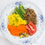 blue and white porcelain bowl filled with shredded carrot, saffrom rice, trimmed green beans, green lentils, tomato and pistachio
