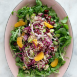 pale pink oval shaped dish of quinoa mandarin cranberry salad on a bed of rocket