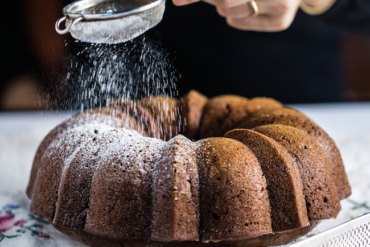 honey cake on flower table cloth with woman's hand sieving confectioner's sugar on top