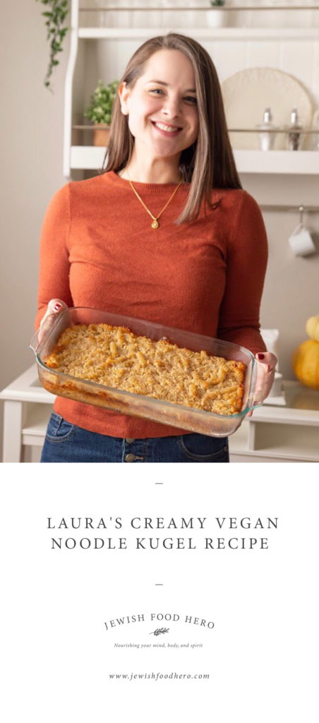 Woman in orange sweater holding on to vegan noodle kugel casserole dish