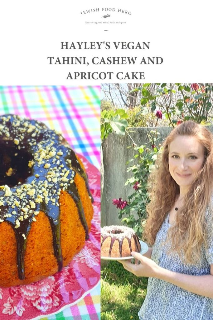 Hayley's Tahini, Cashew and Apricot Cake with a Chocolate Tahini Drizzle on a pink cake stand and chequered tablecloth, Hayley holding the cake in a garden