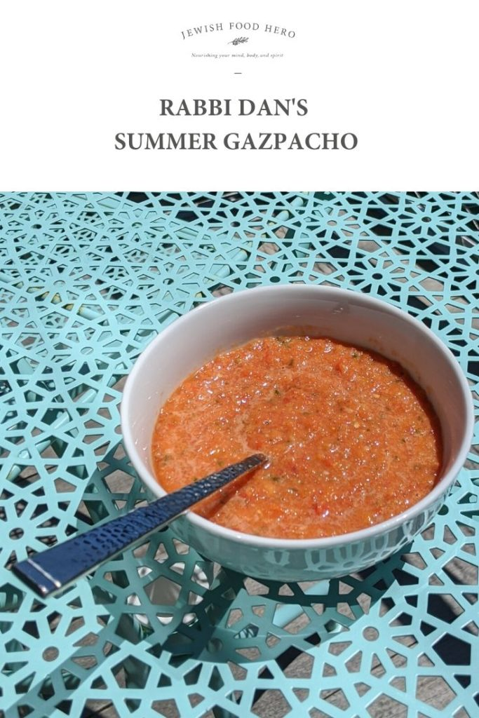 Rabbi Dan sits at a table with a white porcelain bowl of his Summer Gazpacho