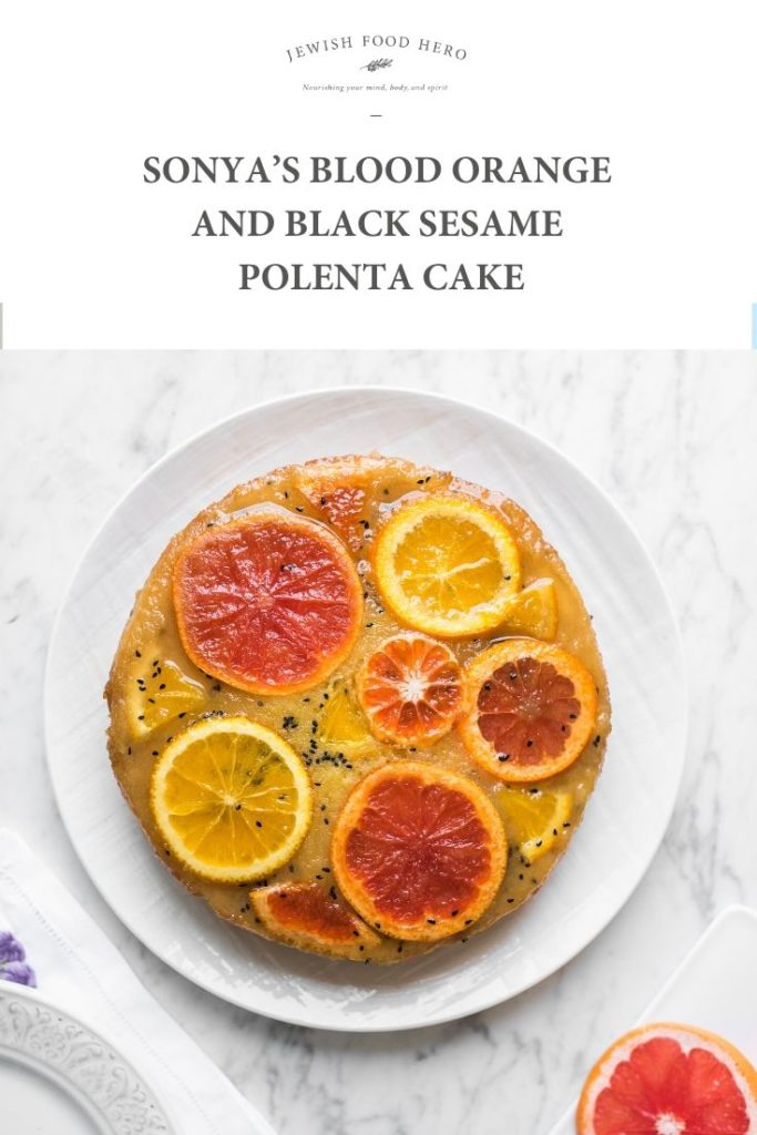 A white porcelain plate with Sonya's Blood Orange and Black Sesame Polenta Cake